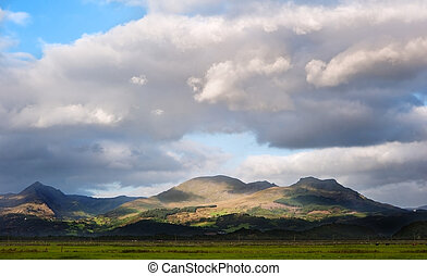 Stunning landscape image panorama view of Snowdon and mountain ranges in National Paark in Wales at sunset