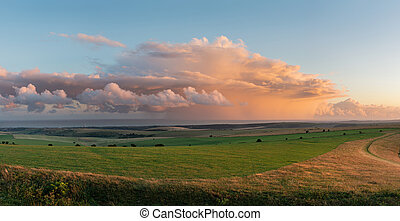 Stunning large panorama of Summer sunset landscape image of South Downs National Park in English countryside with stunning dramatic storm clouds out at sea in the distance
