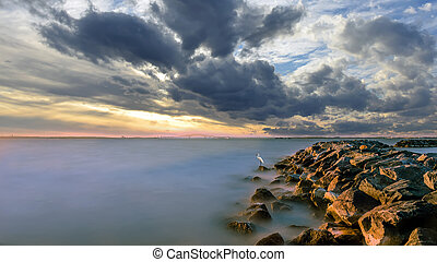 Stunning Long Exposure of the Chesapeake Bay at sunset with a Great Egret standing at the End of a Rock Jetty