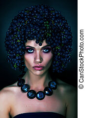 Stunning model brunette in crown of grapes closeup portrait