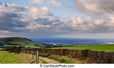 Stunning moody sky with beautiful cloud formations and colors over countryside landscape of path leading into distance