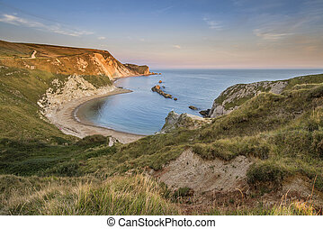 Stunning natural cove coastal landscape at sunset with beautiful vibrant sky
