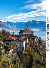 Stunning panorama view of Madonna del Sasso church above Locarno city on cliff with Lake Maggiore, snow covered Swiss Alps mountain peaks and blue sky cloud in background in autumn, Ticino, Switzerland