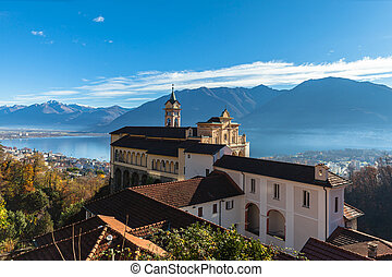 Stunning panorama view of Madonna del Sasso church above Locarno city with Lake Maggiore, snow covered Swiss Alps mountain and blue sky cloud in background on autumn sunny day, Ticino, Switzerland
