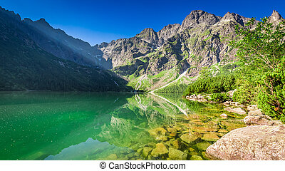 Stunning pond in the mountains at sunrise in summer