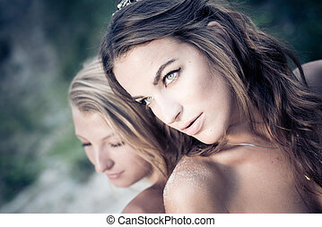 stunning sandy sensuality: portrait of 2 beautiful glamor best girlfriends with naked shoulders having fun posing back to back on green garden sunny outdoors copy space background