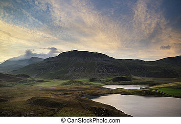 Stunning Summer dawn over mountain range with lake and beautiful