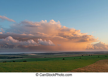 Stunning Summer sunset landscape image of South Downs National Park in English countryisde with orange rain clouds out to sea