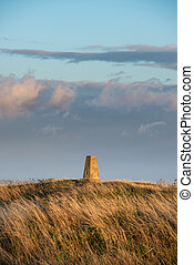 Stunning Summer sunset landscape image of trig point in...