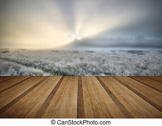 Stunning sun beams light up fog through thick fog of Autumn Fall frosty landscape with wooden planks floor