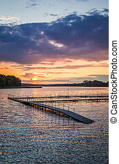 Stunning sunset at the lake with dynamic sky in summer