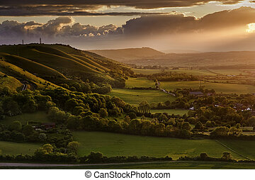 Lovely image of sunburst and beams lighting up sides of hills in beautiful countryside landscape
