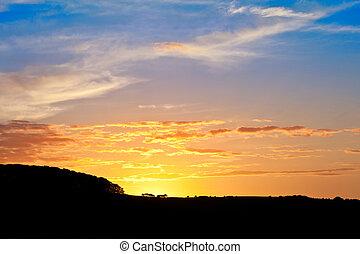 Stunning sunset sky with silhouette landscape horizon
