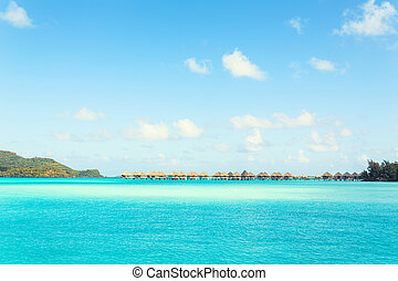Stunning view of blue turquoise lagoon and far bungalows on background of Bora Bora island, French Polynesia