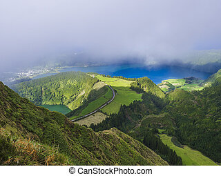 Stunning view on volcanic lakes. Green Lagoa de Santiago and blue Lagoa Azul with Sete Cidades village, partially covered by fog mist and clouds. Sao Miguel in the Azores, Portugal