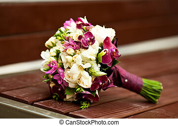 Stunning wedding bouquet decorated with violet ribbon lies on the bench