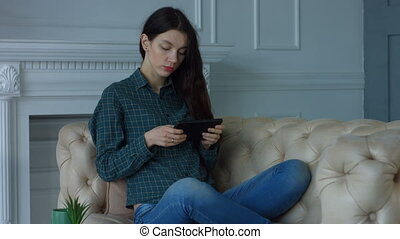 Stunning woman resting with digital tablet at home
