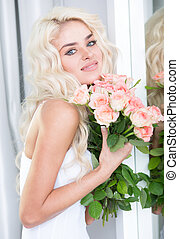 Stunning young blond woman with roses