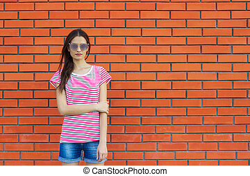 Stunning young woman posing outdoor over brick wall.