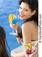 Stunningly beautiful young latina Hispanic woman laughing and  drinking a cocktail by a blue swimming pool with her friend in the foreground.
