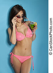 Stunningly beautiful young sexy brunette woman in drinking a...