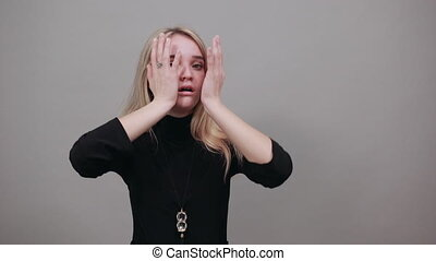 Stupefied beautiful young caucasian over isolated background expresses excitement and thrill, keeps jaw dropped, hands on cheeks, has eyes popped out. Portrait of a scared in studio. Screaming