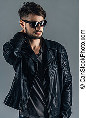 Style and fashion. Confident young man in sunglasses looking away while standing against grey background