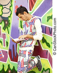 Style boy with laptop near graffiti wall.