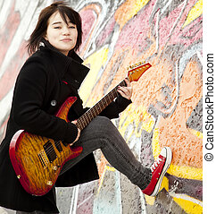 Style brunette girl with guitar.