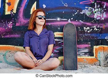 Style girl with skateboard near graffiti wall.