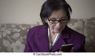 Style grandmother in her 70s using smartphone, smiling,...