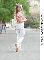 Style icon. Adorable small girl in street fashion style on summer day. Little cute child with beautiful long hair style. Her style is fashionable