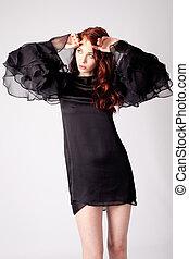 style - red hair womanin elegant black dress, studio shot