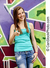 Style teen girl near graffiti background.