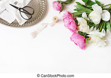 Styled stock photo. Feminine wedding or birthday table composition with floral bouquet. White and pink peonies flowers, old vintage scissors, silver tray and silk ribbons. White background.