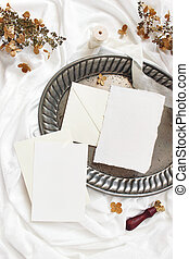 Styled stock photo. Winter, fall wedding, birthday table composition. Stationery mockup scene. Greeting cards, envelopes, dry hydrangea flowers. Silver tray on silk fabric. Vertical flat lay, top view