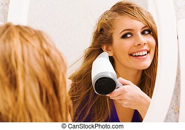 Image of pretty female looking in mirror while drying her hair