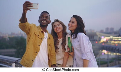Stylish African American guy is taking selfie with cute...