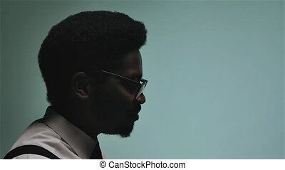 Stylish African American in glasses and white shirt sings ...
