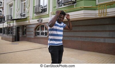 Stylish african american man dancing in city street