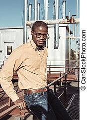 Stylish african american man sitting on guardrails
