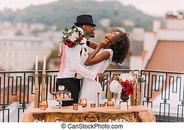 Stylish african wedding couple having fun on the balcony with luxury golden table in oriental style on foreground