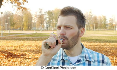 Stylish and fashionable man with a beard vape and smiling,...