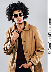Stylish and handsome. Confident young African man in sunglasses looking away and adjusting his coat while standing against grey background