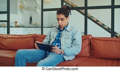 Stylish arabic man with tablet pc relaxing on sofa