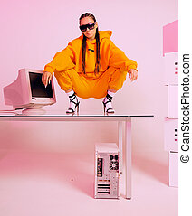Stylish asian female office worker with obsolete computer squats on desk. Colored Neon light