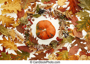 Stylish Autumn Flat Lay. Happy Thanksgiving. Pumpkin in beautiful fall leaves wreath, berries, nuts, acorns, cones on rustic white background top view. Seasons greetings.