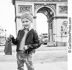 happy elegant child with red present bag in Paris, France
