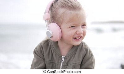 Stylish baby in pink headphones listening to music.