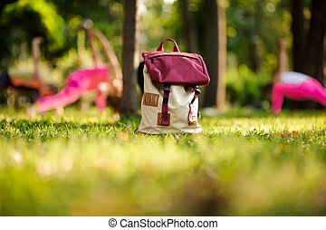 Stylish backpack on grass in a green park on summer day